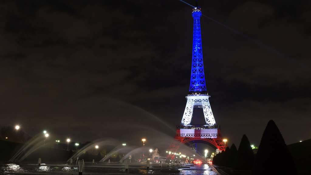 A photo taken on November 16, 2015 in Paris shows the Eiffel Tower illuminated with the colors of the French flag in tribute to the victims of the November 13, 2015 Paris terror attacks. AFP PHOTO / ALAIN JOCARD