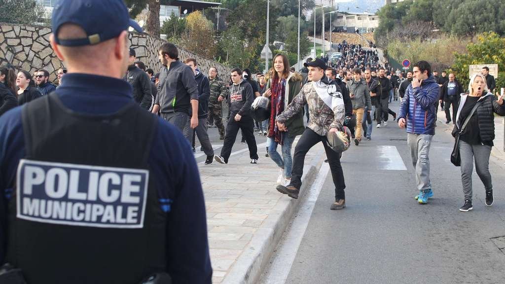 A police officer stand guards as people take part in a demonstration in Ajaccio on December 27, 2015, after France banned demonstrations in part of the Corsican capital Ajaccio following two days of anti-Arab protests and sectarian tensions. Several hundred people in Corsica defied a ban on demonstrations imposed in a flashpoint area of the capital Ajaccio today after two days of violent anti-Arab protests. AFP PHOTO / YANNICK GRAZIANI