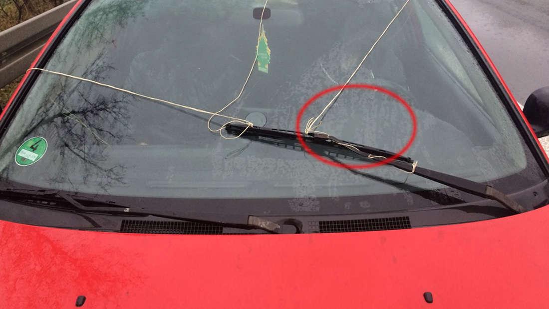 Scheibenwischer kaputt?! Mit einer Paketschnur per Handbetrieb war ein Autofahrer bei Regen auf der Autobahn unterwegs.