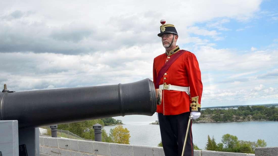 """""""Leftenant Colonel"""" Mark Bennett steht neben einer Kanone in Fort Henry am St.-Lawrence-Strom."""