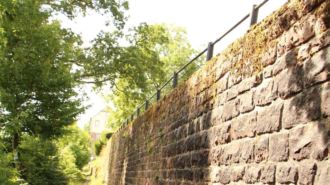 Ein Trampelpfad führt an der Burgmauer entlang.