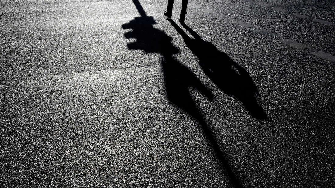 Eine Ampel und eine Frau werfen am 23.01.2013 in M¸nchen (Bayern) Schatten auf eine Strafle. Foto: Victoria Bonn-Meuser/dpa +++(c) dpa - Bildfunk+++