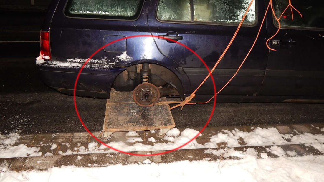 Das Auto hat im wahrsten Sinne des Wortes ein Rad ab. Ein Rollbrett als Ersatzrad ist allerdings eine sehr gefährliche Lösung.