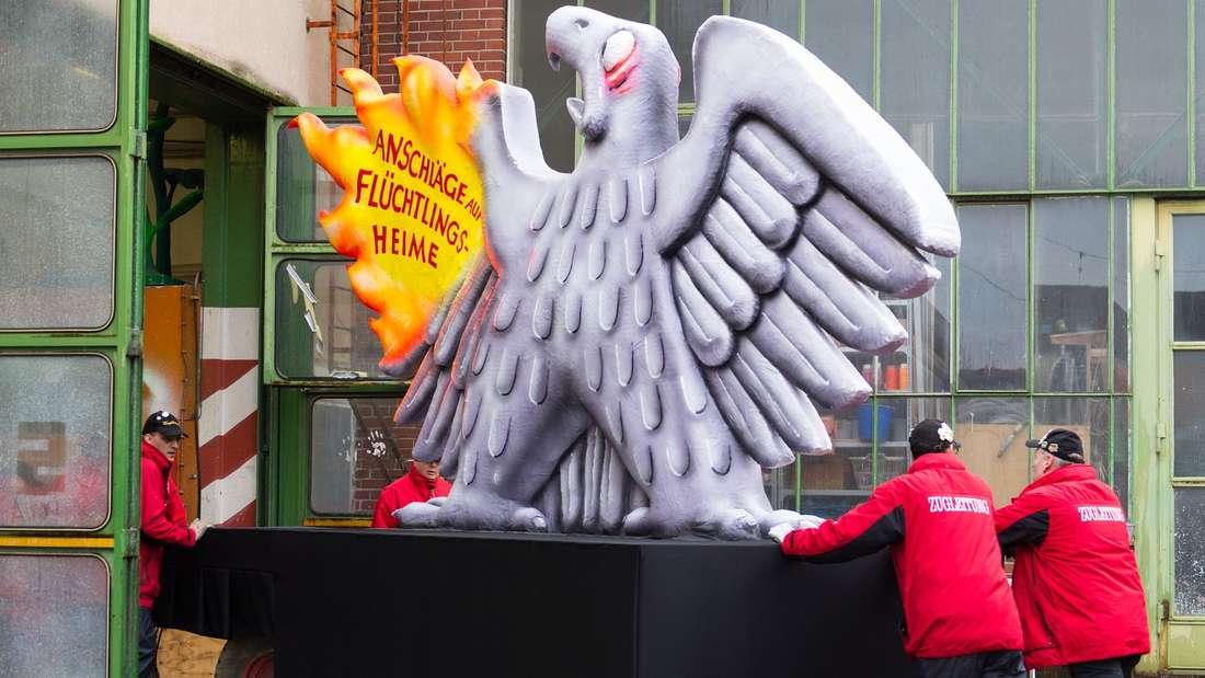 Ein Karnevalswagen mit dem Motiv Â«Anschläge auf Flüchtlingsheime» wird am 08.02.2016 in Düsseldorf (Nordrhein-Westfalen) von den Mitgliedern der Zugleitung in die Wagenbauhalle geschoben. Wegen des heftiger werdenden Sturms ist der Düsseldorfer Rosenmontagszug abgesagt worden. Foto: Monika Skolimowska/dpa +++(c) dpa - Bildfunk+++