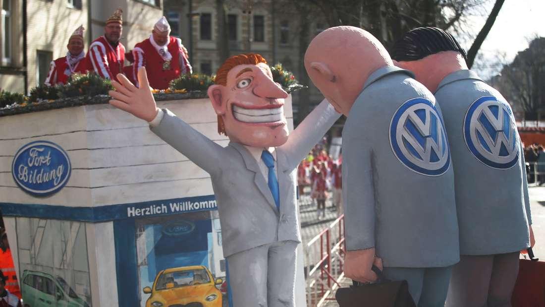 """Karnevalisten ziehen am Rosenmontag (08.02.2016) mit einem Motivwagen unter dem Motto """"Köllsche Willkommenskultur"""" durch Köln (Nordrhein-Westfalen). Der Kölner Rosenmontagsumzug findet trotz einer Sturmwarnung statt, allerdings mit Einschränkungen."""