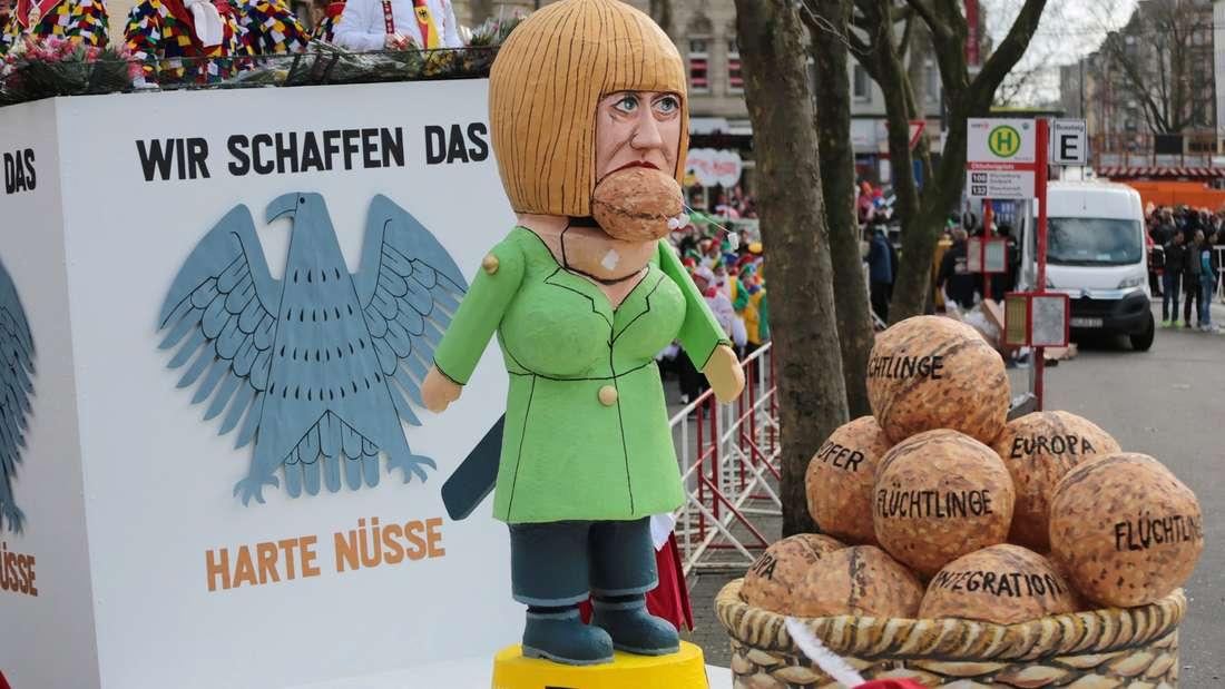 Karnevalisten ziehen am Rosenmontag (08.02.2016) mit einem Motivwagen, der Bundeskanzlerin Angela Merkel beim knacken harter Nüsse zeigen soll, durch Köln (Nordrhein-Westfalen). Der Kölner Rosenmontagsumzug findet trotz einer Sturmwarnung statt, allerdings mit Einschränkungen.