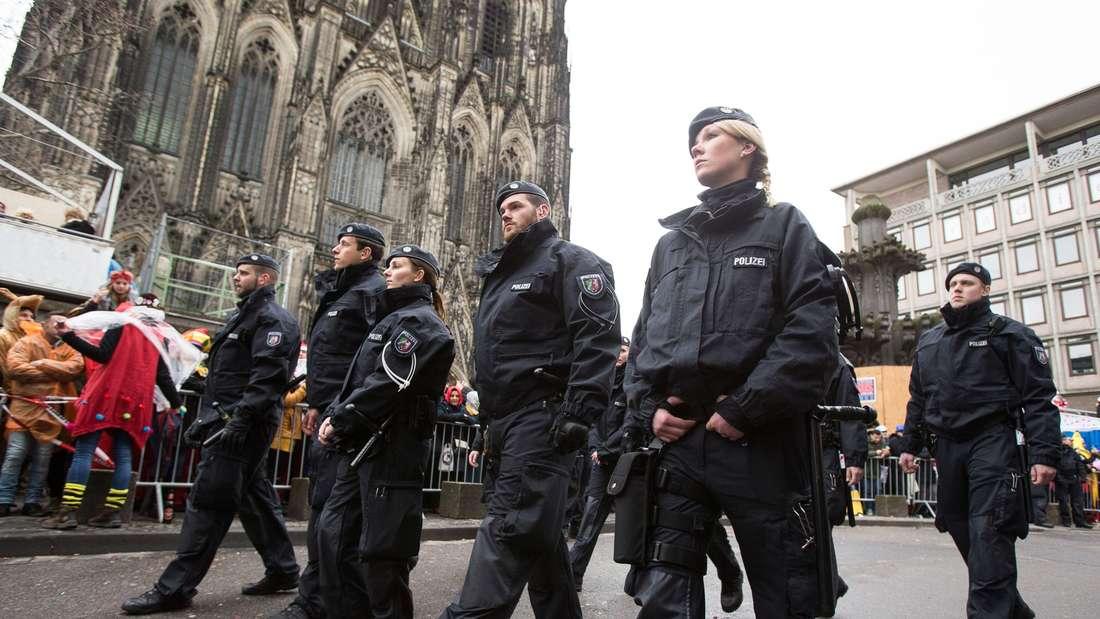 Polizisten begleiten am 08.02.2016 vor dem Dom in Köln (Nordrhein-Westfalen) den Rosenmontagszug. Der Kölner Rosenmontagsumzug findet trotz einer Sturmwarnung statt, allerdings mit Einschränkungen.