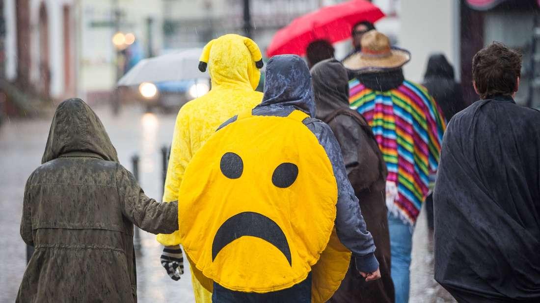 Karnevalisten gehen am 08.02.2016 in Seligenstadt (Hessen) bei starkem Regen durch die Altstadt, nachdem der traditionelle Rosenmontagszug wegen einer Sturmwarnung abgesagt worden war.