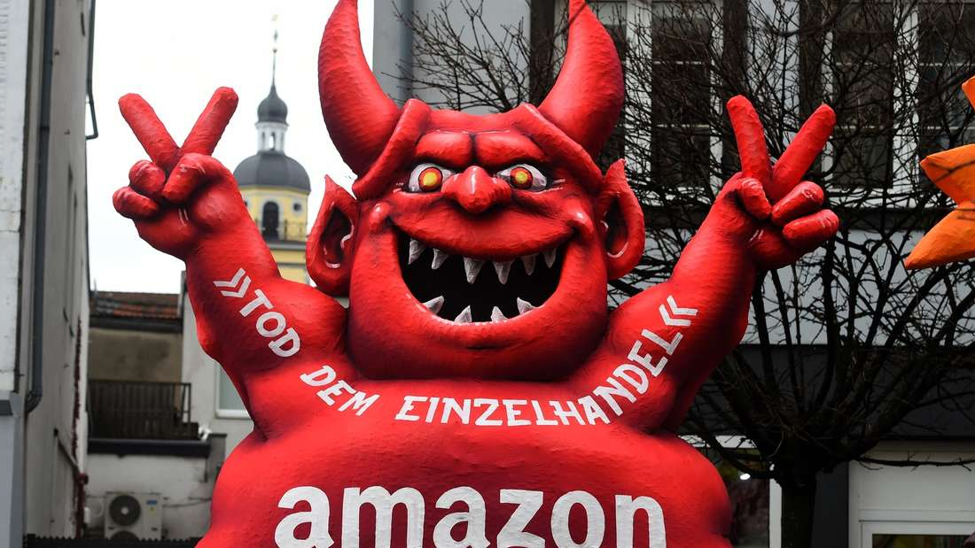 """A carnival float, depicting a red devil reading """"Death of Retail - Amazon"""", stands in front of the city hall in Duesseldorf, western Germany, after the Rose Monday (Rosenmontag) street parade has been cancelled on February 8, 2016."""