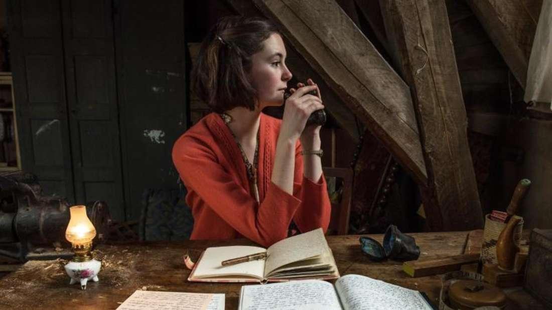 Lea van Acken schreibt als Anne Frank in einer Kammer unterm Dach an ihrem Tagebuch. Foto: Zeitsprung Pictures, AVE & Universal Pictures Production