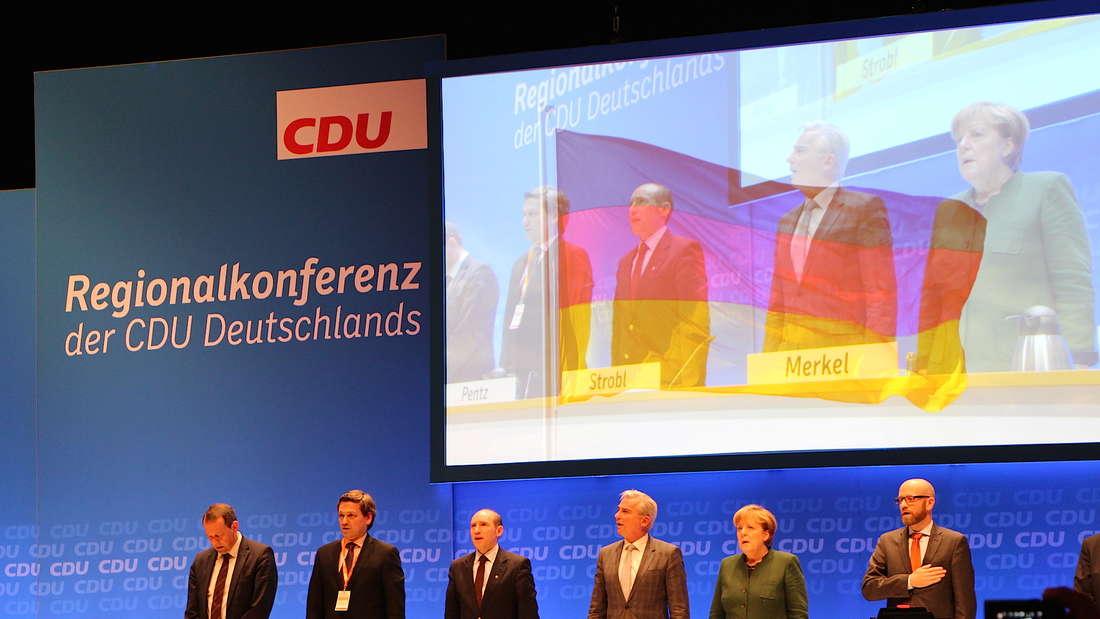 Für die deutsche Nationalhymne erheben sich alle im Saal.