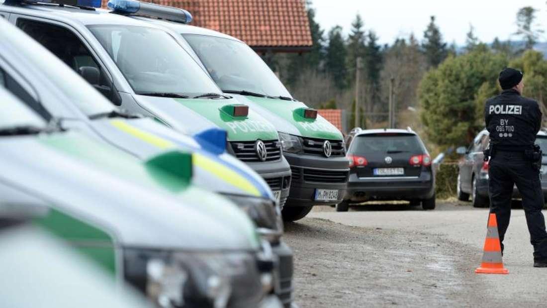 Einsatzwagen der Polizei unweit des Tatortes. Zwei Menschen wurden offenbar vonEinbrechern getötet. Foto: Andreas Gebert