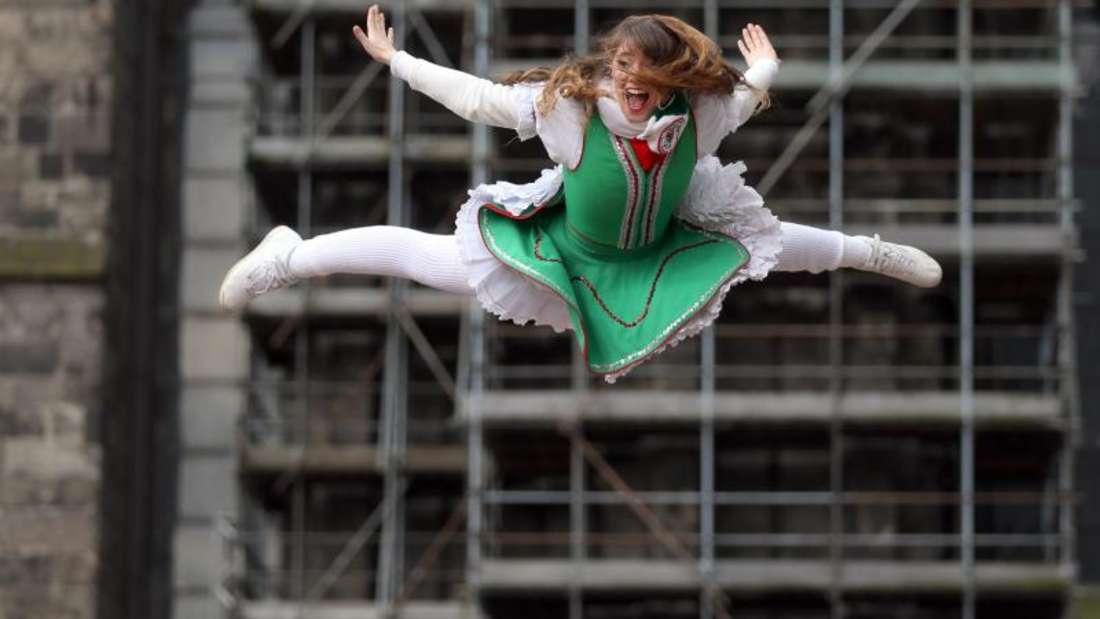 Eine Karnevalistin «fliegt» über den Köpfen der Zuschauer beim Rosenmontagszug vor dem Kölner Dom. Foto: Rolf Vennenbernd