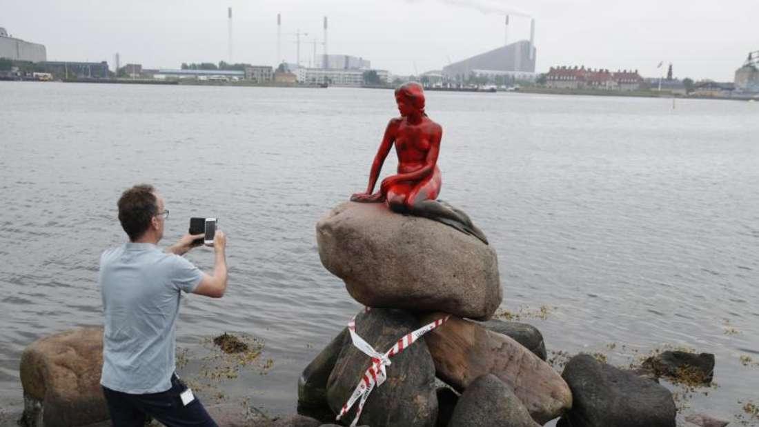 Ein Mann fotografiert die mit roter Farbe beschmierte Statue der kleinen Meerjungfrau im Hafen von Kopenhagen. Foto: Dresling Jens