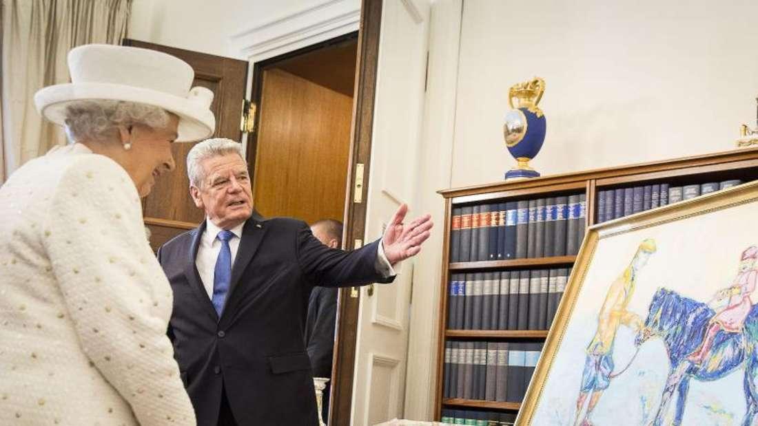 Bundespräsident Joachim Gauck und Königin Elizabeth II. 2015 mit dem Gemälde «Pferd in Royalblau» von Nicole Leidenfrost im Schloss Bellevue. Foto: Jesco Denzel