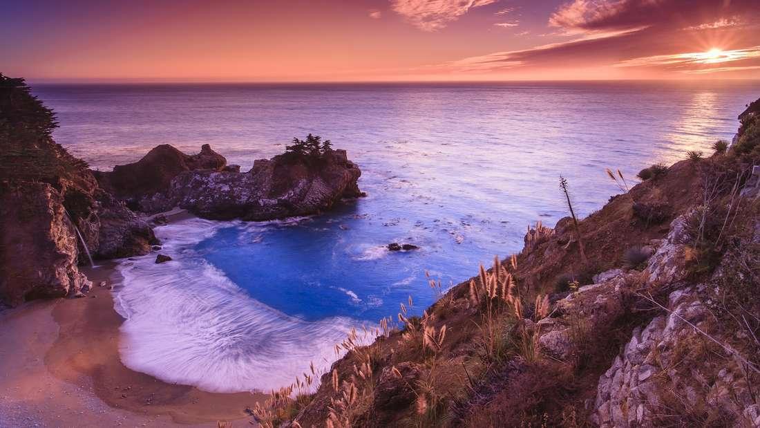 Pfeiffer Beach, Kalifornien, USA: Für Fans von Sonnenuntergängen hält der Pfeiffer Beach ein besonderes Farbenspiel bereit: Durch die letzten Sonnenstrahlen des Tages und die Kristalle im Sand schimmert der Strand in einem blassen Violett. Da der Strand am Highway 1 nicht ausgeschildert ist, haben Urlauber die Chance, das Naturschauspiel ohne großen Menschenandrang zu beobachten.
