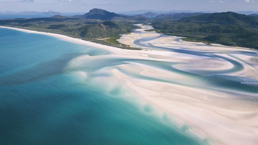 Die Strandabschnitte von Whitehaven Beachbestehen hier zu fast 99 Prozent aus Quarz, weshalb sie sich mit einer besonders hellen Sandfarbe hervorheben. Grüne Hügel und Wasser in verschiedenen Blautönen umgeben den Strand und machen ihn so einzigartig farbenfroh.