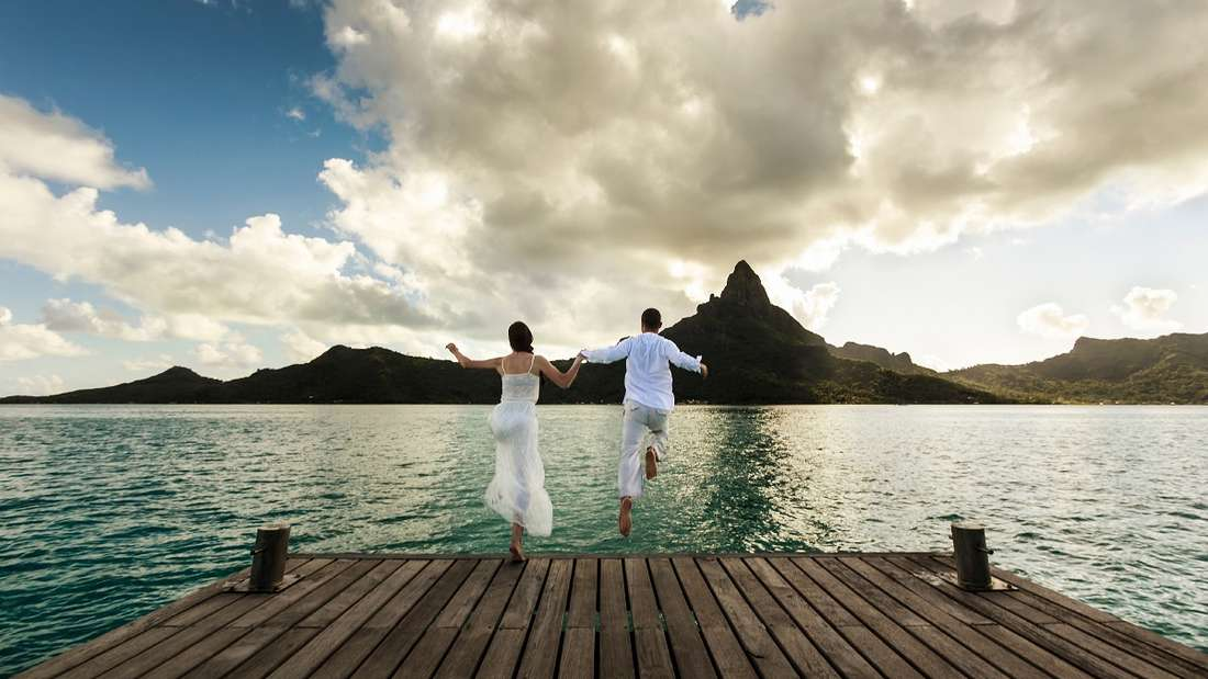 Ein junges Ehepaarspringt von einem hölzernen Pier in das wunderbare Meer von Bora Bora in Französisch-Polynesien.