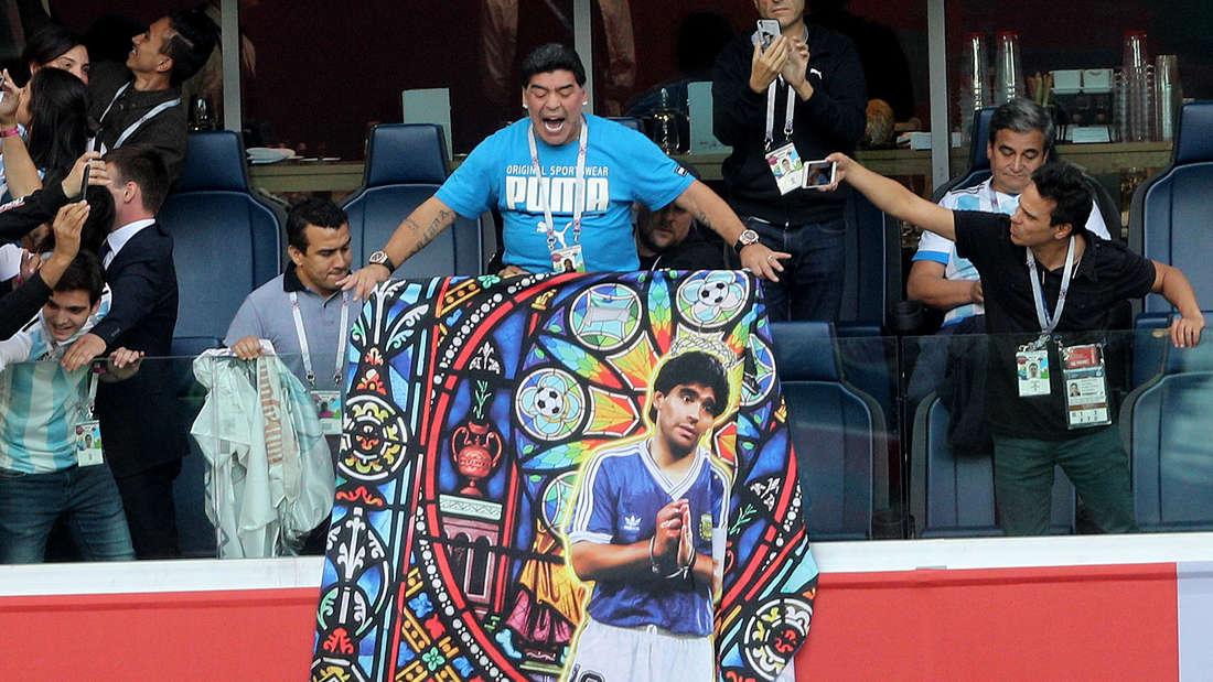 Maradona mit dem Banner, das ihn wie einen Heiligen darstellt.