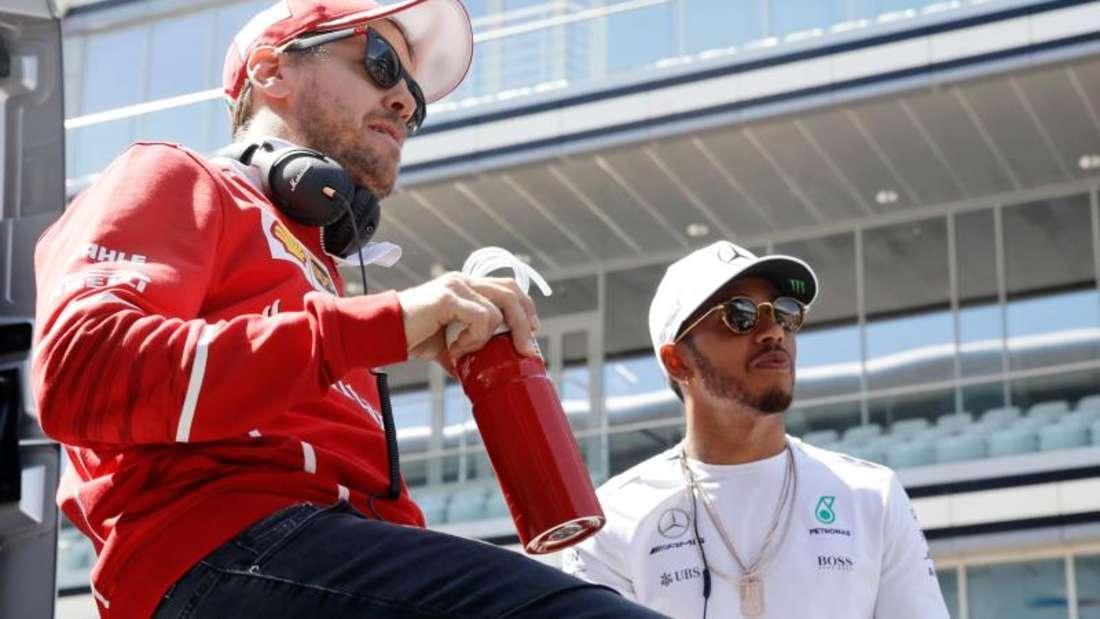 Konkurrenten: Sebastian Vettel (l) und Lewis Hamilton. Foto: Pavel Golovkin/AP