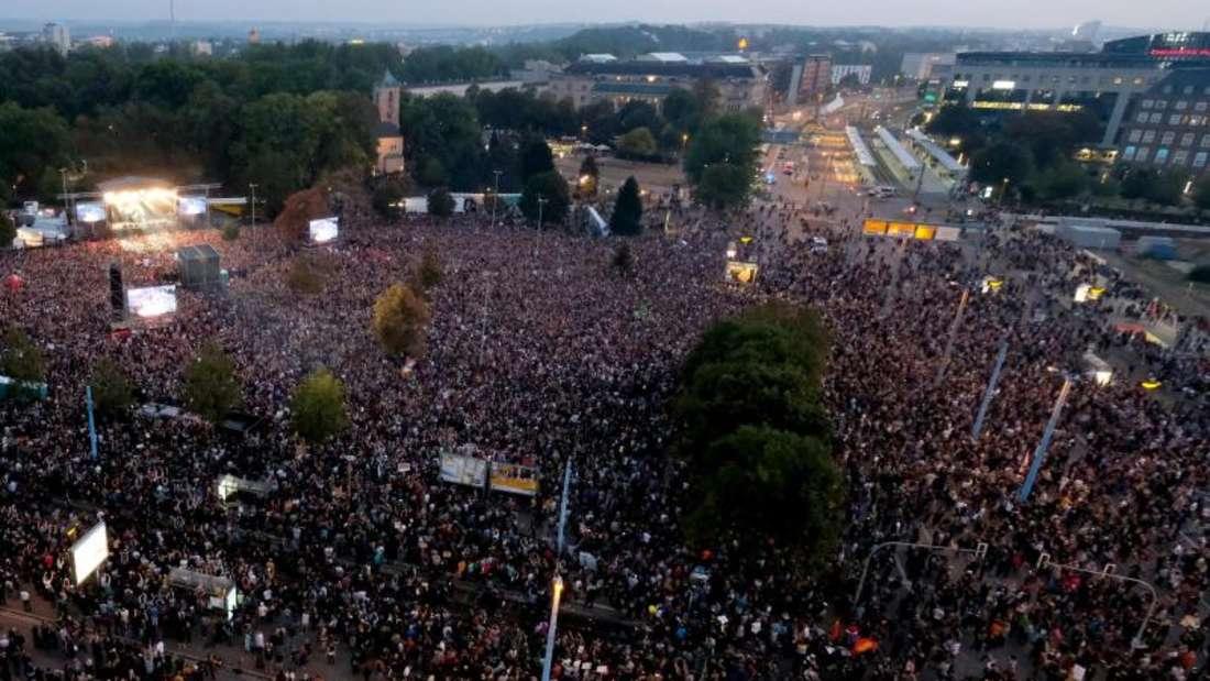 Zuschauer stehen während des Konzerts unter dem Motto «#wirsindmehr» auf dem Parkplatz vor der Johanniskirche. Foto: Sebastian Willnow