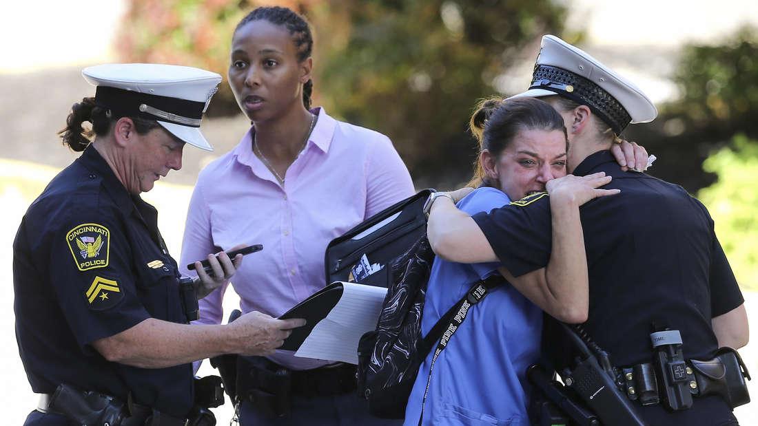 Eine Frau wird vor der Notaufnahme des University of Cincinnati Medical Center von einer Beamtin getröstet.