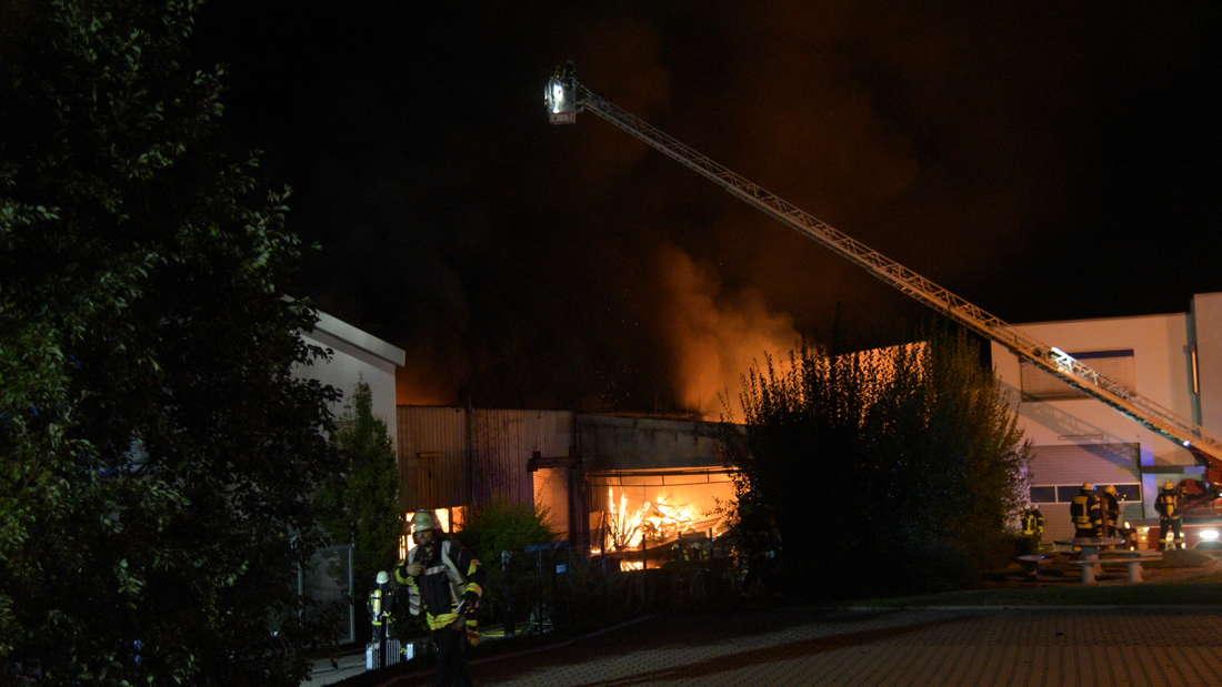 Mehrere Hallen einer Recyclingfirma stehen in Flammen.