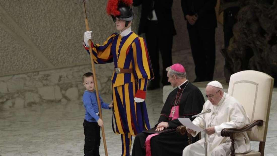 Ein Kind möchte mit einem Mitglied der päpstlichen Schweizergarde spielen. Foto: Gregorio Borgia/AP