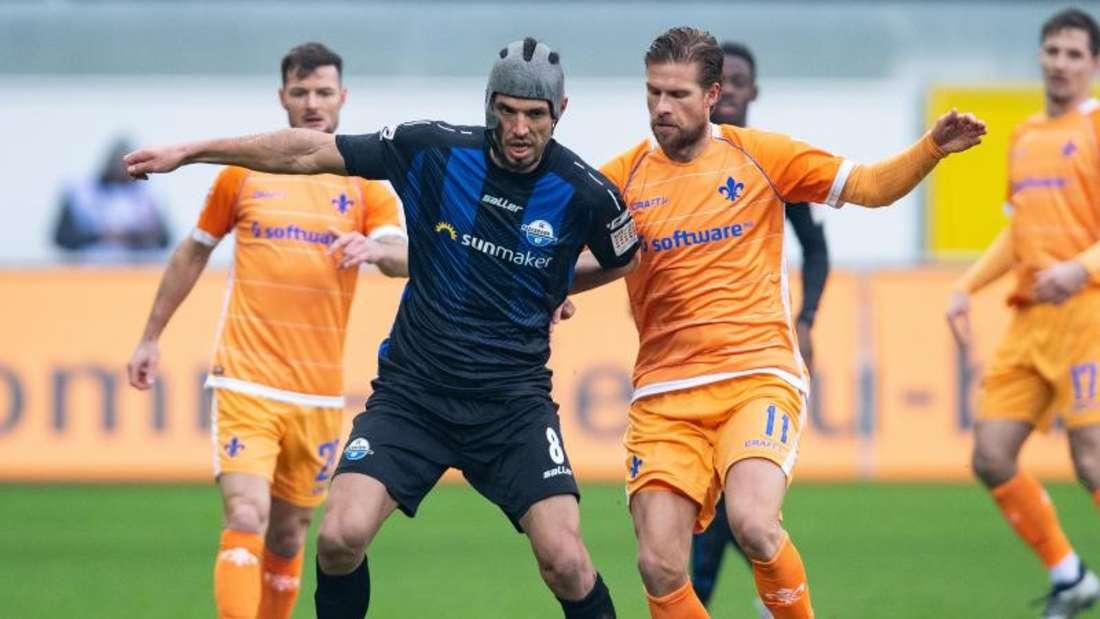 Paderborns Klaus Gjasula (l) kann sich mit dem Ball gegen Tobias Kempe von Darmstadt 98 behaupten. Foto: Guido Kirchner