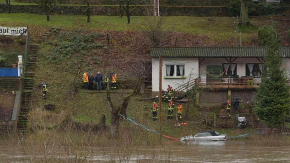 Die Feuerwehr sichert ein 3er BMW Cabrio in Eberbach-Pleutersbach, damit es nicht vom Hochwasser mitgenommen wird