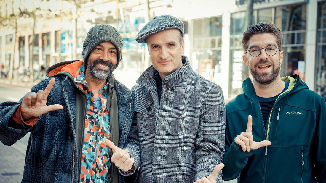 Die Grünen-Politiker Derek Cofie-Nunoo (links) und Felix Grädler (rechts) zusammen mit Hip-Hop-Legende Toni-L.