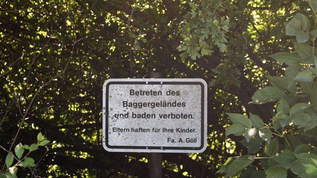Ein Schild verbietet das Schwimmen an dem Baggersee in Bruchsal-Büchenau.