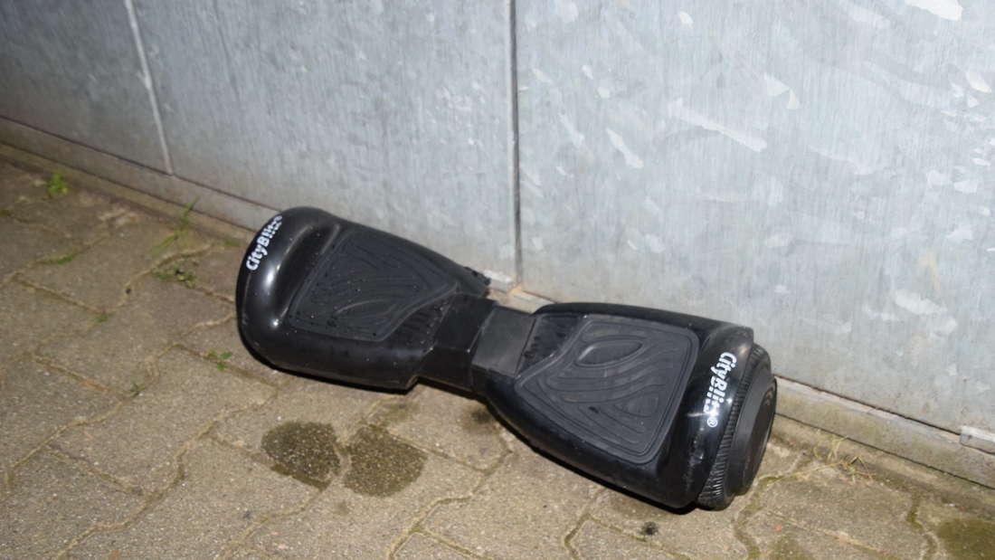 Der Vater bringt das Hoverboard ins Freie.