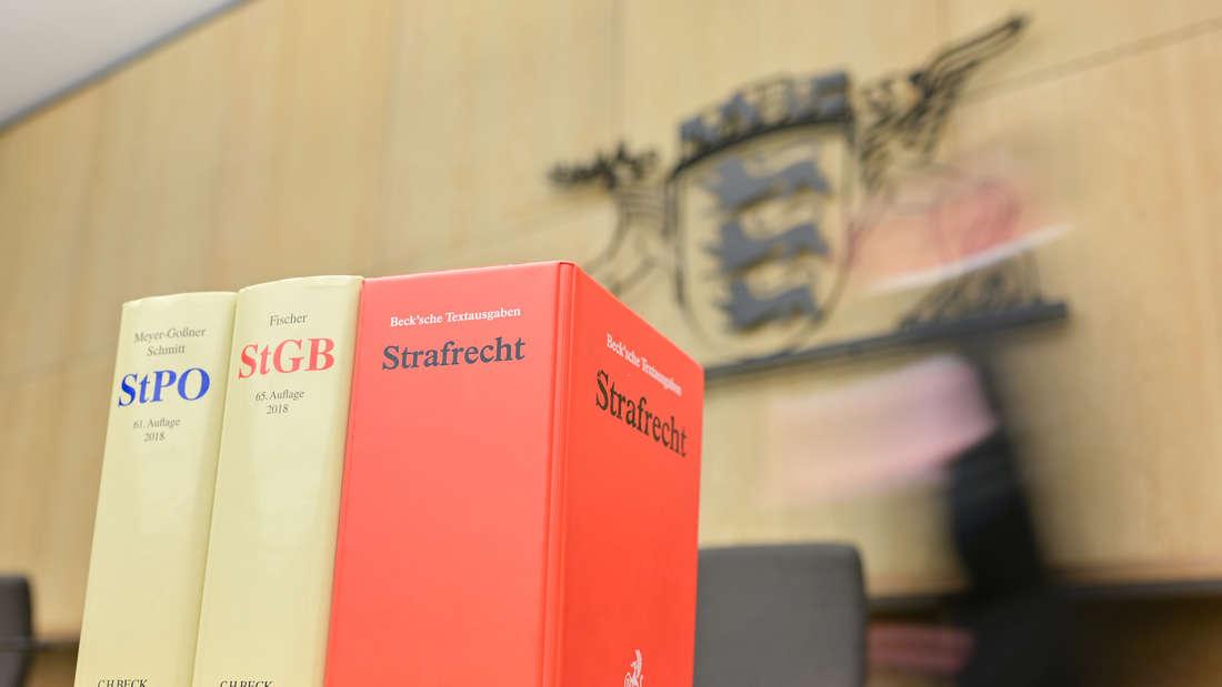 Drei Gesetzesbücher stehen auf dem Tisch des Mannheimer Landgerichts, dahinter läuft eine verschwommene Figur.