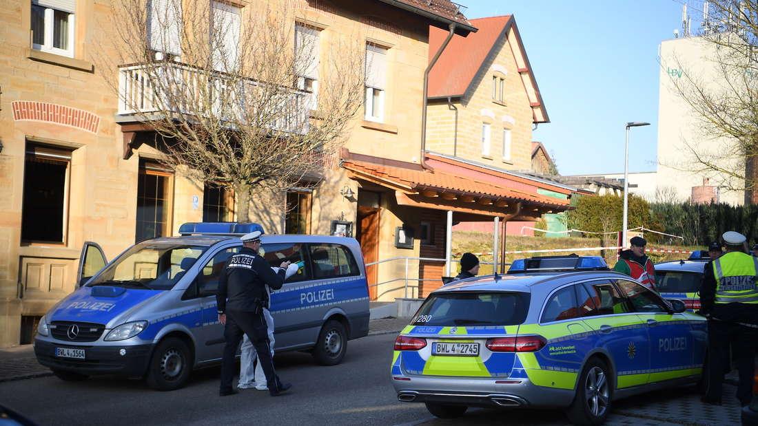 Rot Am See: Nach Schüssen in Rot am See im Nordosten Baden-Württembergs stehen Polizeiautos an einem Haus. Hier sollen mehrere Menschen getötet worden sein. Ein Tatverdächtiger sei festgenommen worden, sagte die Polizei.