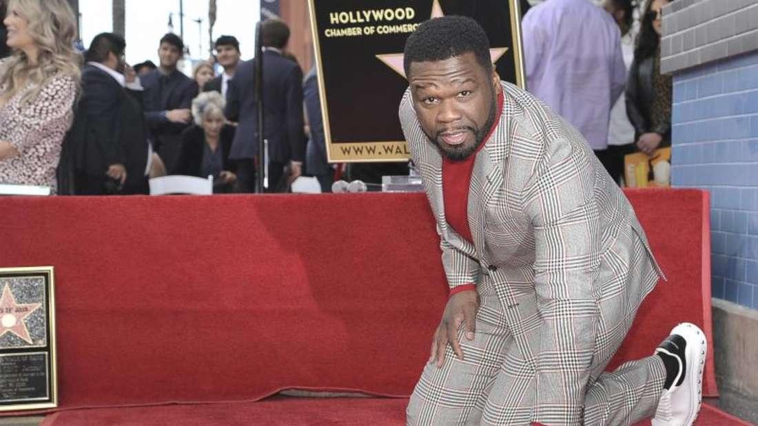 «50 Cent» kniet während der Zeremonie zur Ehrung auf dem «Walk of Fame» neben seinem Stern. Foto: Richard Shotwell/Invision/AP/dpa