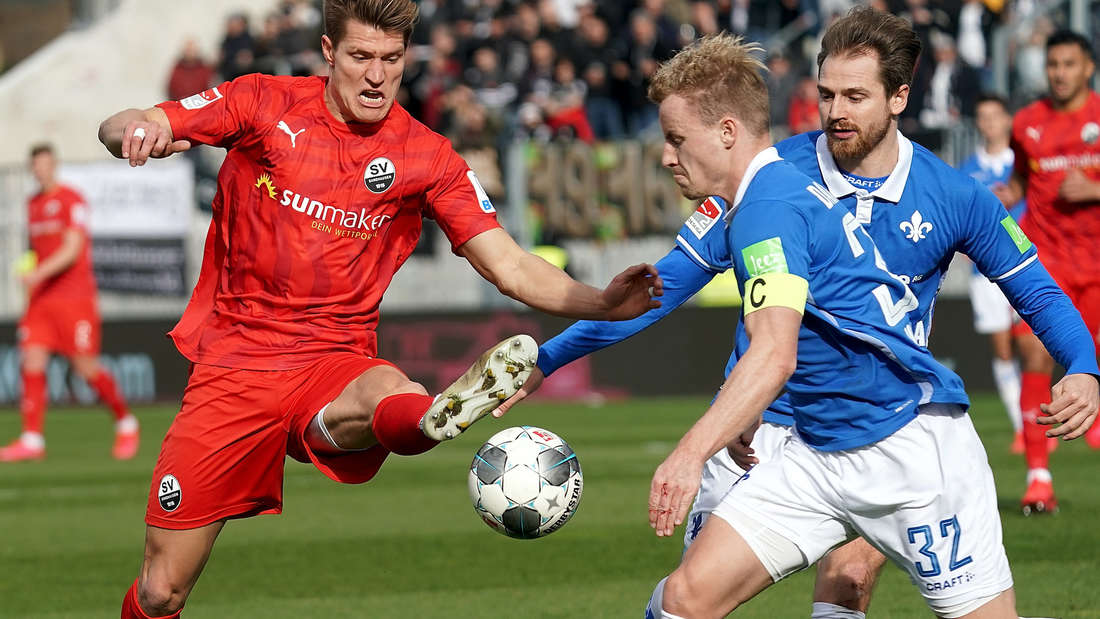 Kevin Behrens (l) kommt vor den Darmstädtern Immanuel Höhn (r) und Fabian Holland (M) an den Ball.
