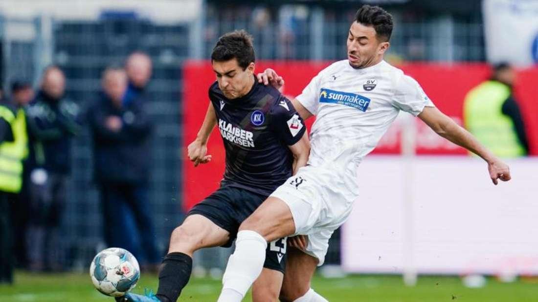 Karlsruhes Dirk Carlson (l) und Sandhausens Aziz Bouhaddouz kämpfen um den Ball. Foto: Uwe Anspach/dpa
