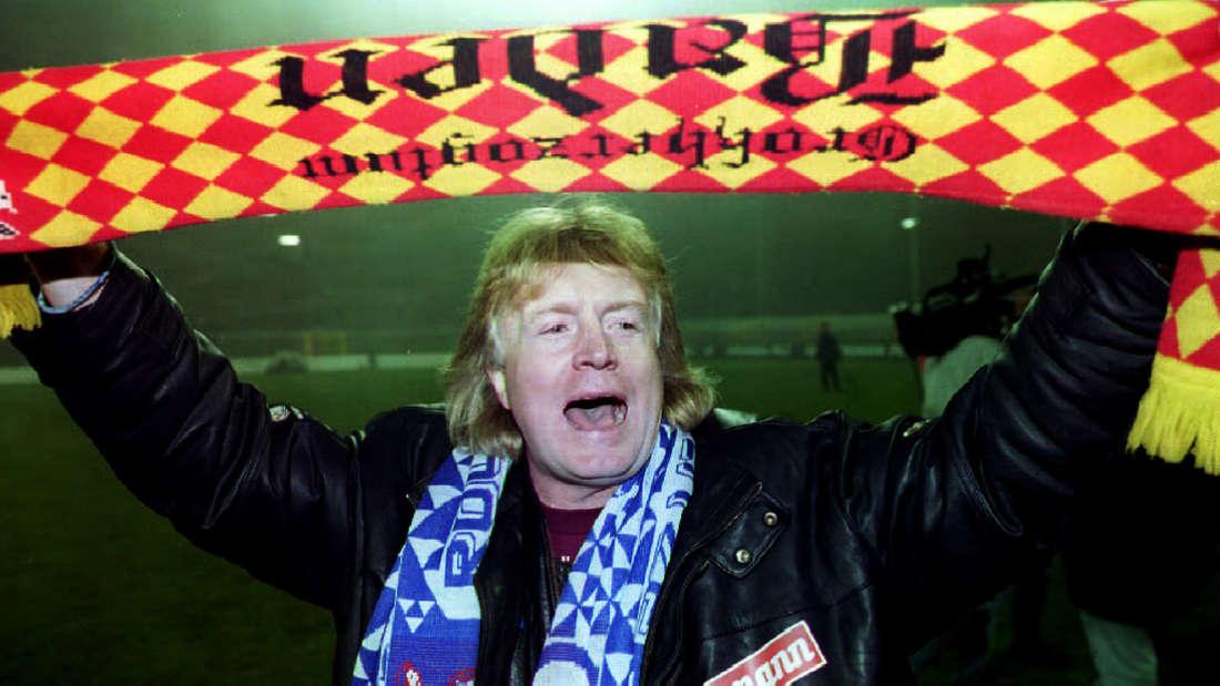 Erfolgstrainer Winfried Schäfer jubelt mit einem KSC-Schal.