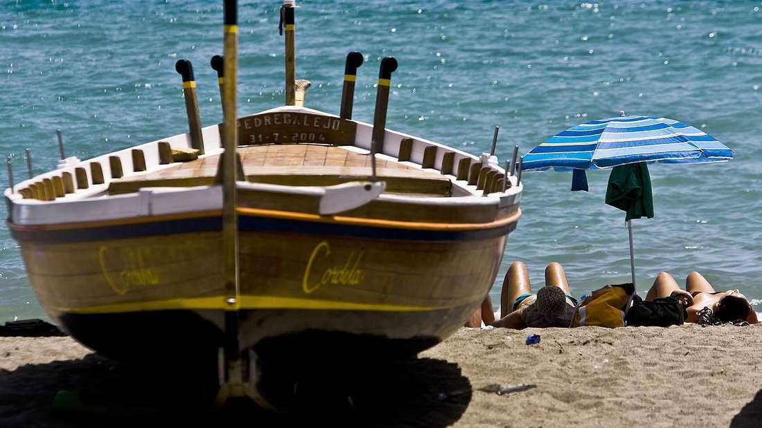 Sonnenbaden am Strand von Malaga in Andalusien.