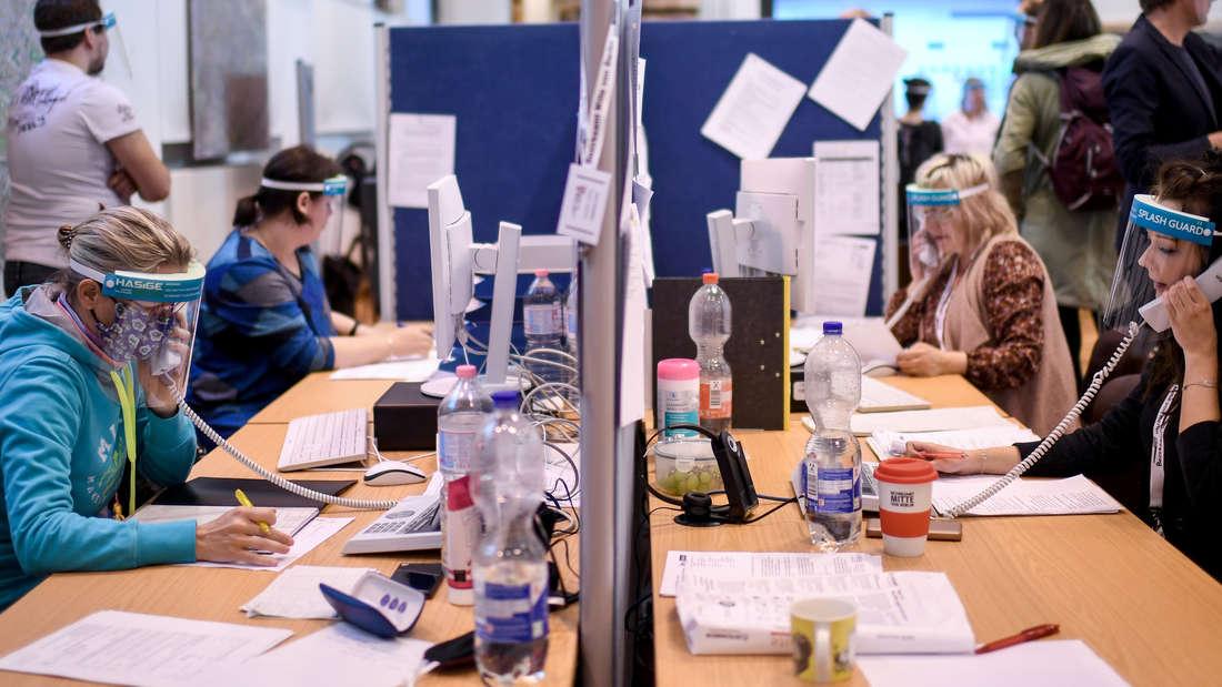Mitarbeiter des Gesundheitsamtes Mitte mit Gesichtsschutzschirm telefonieren im Lagezentrum des Gesundheitsamt Mitte (Symbolbild).