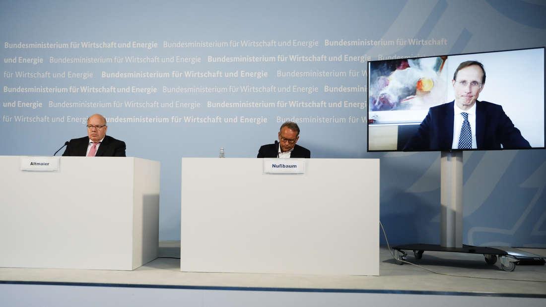 Peter Altmaier und Ulrich Nußbaum sitzen bei einer Pressekonferenz. Über einen Bildschirm ist Franz-Werner Haas zugeschaltet.