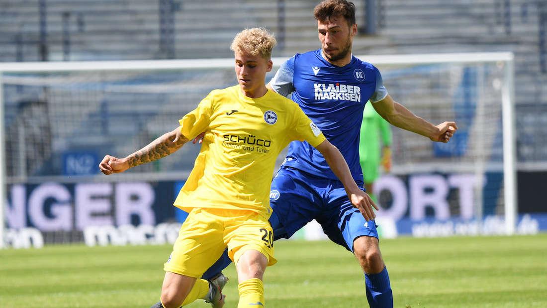 Der Karlsruher Lukas Fröde (r) und der Bielefelder Nils Seufert kämpfen um den Ball.