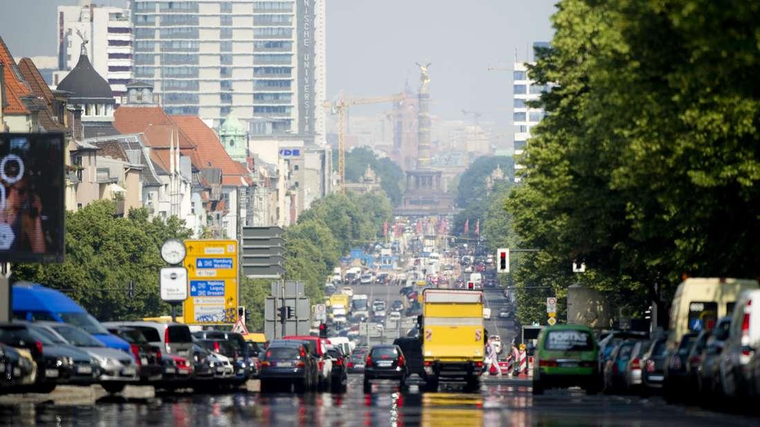 Auf einer Straße stehen Autos vor einer Ampel. Dahinter Berlin.