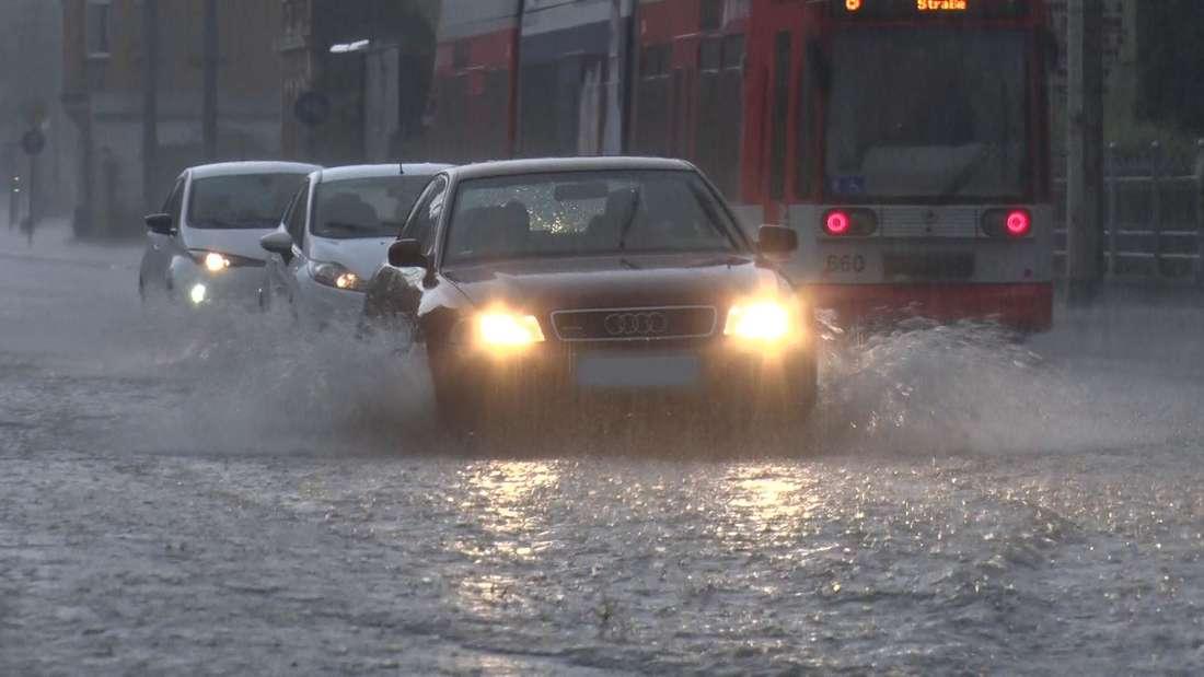 Mehrere Autos fahren über eine vom Regen überflutete Straße. (Symbolfoto)