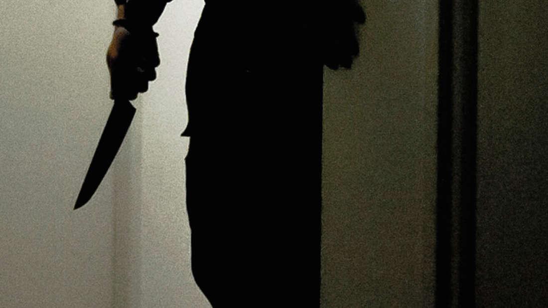 Eine Person steht mit einem Messer in einem Raum. Alles ist dunkel.