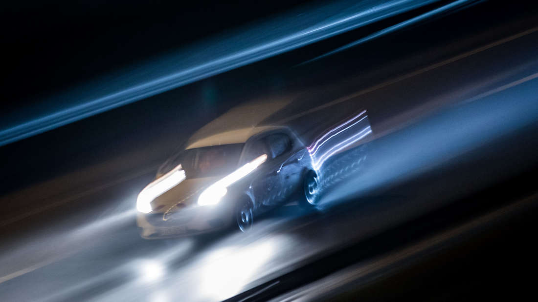 Ein verschwommenes Auto rast bei Nacht über die Straße.