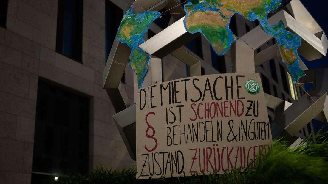 Denkmal in Heidelberg mit Protestplakat geschmückt.