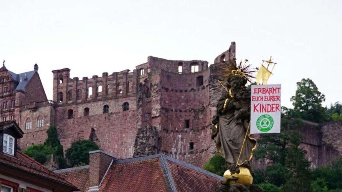 Denkmal in Heidelberg mit Protestplakat geschmückt. Im Hintergrund das Heidelberger Schloss.