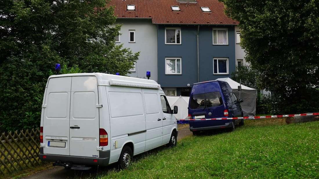 Einsatzfahrzeuge der Polizei stehen vor einer Wohnung in Reutlingen in der mehrere tote Menschen gefunden wurden.